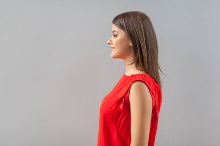 Profile side view portrait of happy beautiful brunette young woman in red shirt standing and looking forward with toothy smile and happiness. indoor, studio shot, isolated on gray background.