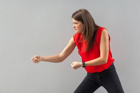 Profile side view portrait of serious beautiful brunette young woman in red shirt standing with fists and try to pulling something or boxing. indoor, studio shot, isolated on gray background.