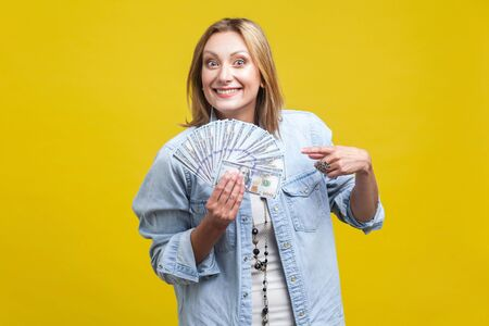 Portrait of happy lottery winner, beautiful woman in denim shirt pointing at fan of dollars, looking at camera with toothy smile, big money, income. indoor studio shot isolated on yellow background Фото со стока