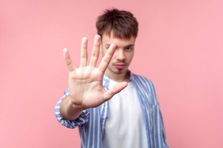 Stop! Portrait of young serious brown-haired man with small beard and mustache in casual striped shirt gesturing stop, showing warning sign at camera. indoor studio shot isolated on pink background