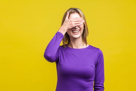 So shameful, I'd rather not watch this! Portrait of bashful positive woman in elegant purple dress covering eyes with hand and laughing, shy to look. indoor studio shot isolated on yellow background