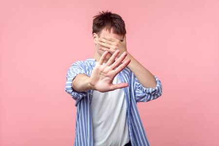 Don't want to look at this. Portrait of brown-haired man in casual striped shirt covering eyes with hand and showing stop gesture, refusing to watch. indoor studio shot isolated on pink background Banque d'images