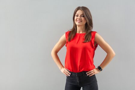 Portrait of happy beautiful brunette young woman in red shirt standing with hands on waist and looking at camera with toothy smile and happiness. indoor, studio shot, isolated on gray background.