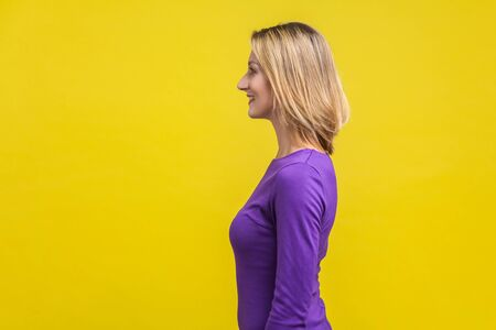 Side view of positive successful woman in purple dress standing with toothy smile, looking happy and content, empty copy space for advertisement . indoor studio shot isolated on yellow background