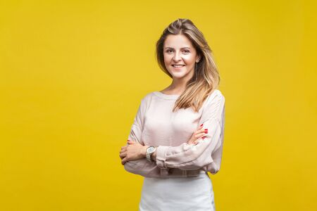 Portrait of happy attractive young woman with fair hair in casual beige blouse standing with crossed arms and looking at camera with toothy smile. indoor studio shot isolated on yellow background