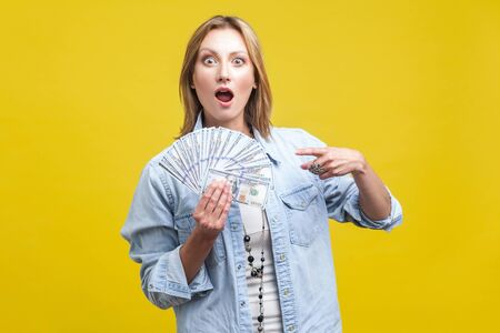 Lottery winner. Portrait of amazed beautiful woman in denim shirt pointing at fan of dollars, looking shocked by big money income, wow expression. indoor studio shot isolated on yellow background