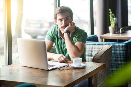 Young thoughtful quizzical businessman in green t-shirt sitting with laptop, hand on chin looking away and thinking what to do. business and freelancing concept. indoor shot near big window at daytime Stock fotó