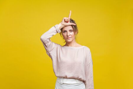 Portrait of serious upset woman with fair hair in casual beige blouse standing, showing loser gesture with fingers on her head, looking at camera. indoor studio shot isolated on yellow background Reklamní fotografie