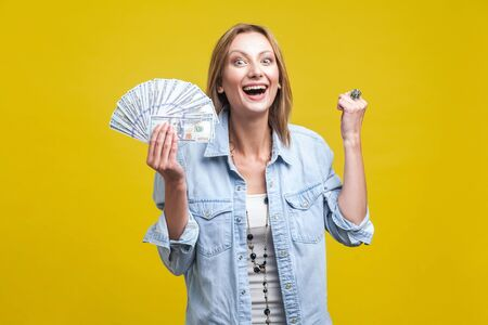 Portrait of extremely happy woman in denim shirt holding fan of dollars, smiling with teeth and showing yes i did it gesture, celebrating big income. indoor studio shot isolated on yellow background