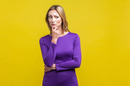 Portrait of confused puzzled woman in tight purple dress standing holding her chin and looking aside while thinking intensely, having doubts suspicion. indoor studio shot isolated on yellow background