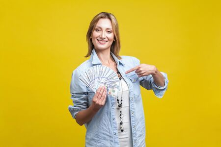 I earned big money! Portrait of proud woman in casual denim shirt pointing at herself and holding dollars, looking arrogant at camera, boasting about income. indoor studio shot isolated on yellow