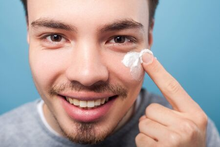 Male skincare cosmetics. Portrait of happy handsome man with small beard and mustache applying cream or anti-aging cosmetics on face, looking at camera. studio shot isolated on blue background