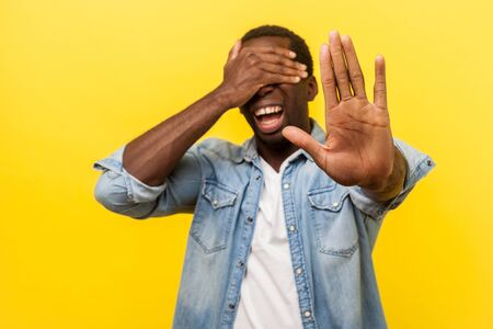 No, I don't want to watch. Portrait of scared panicked man in denim casual shirt standing with covered eyes and showing stop gesture, afraid to look. indoor studio shot isolated on yellow background