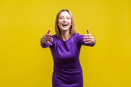 Come into my arms, free hugs! Portrait of adorable hospitable woman in elegant tight purple dress smiling and reaching out hands, going to embrace. indoor studio shot isolated on yellow background 写真素材