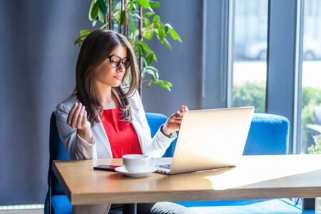 Portrait of beautiful stylish brunette young woman in glasses sitting, looking at her laptop screen on video call and showing money gesture. indoor studio shot, cafe, office background.