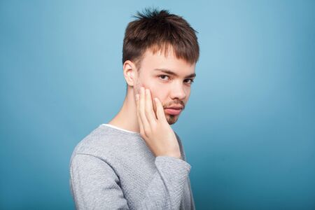 Portrait of young brunette man with small beard and mustache in casual sweater touching bristle on cheek, looking serious at camera, male skincare and grooming concept. studio shot isolated on blue