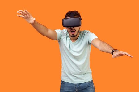 Portrait of frightened gamer, brunette man in t-shirt wearing vr glasses, stretching hands forward, trying to grab something while playing virtual reality game, scared shocked face. indoor studio shot