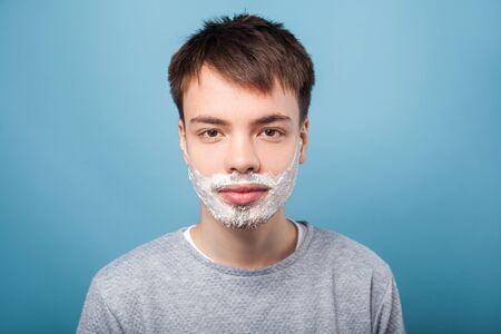 Portrait of young calm man in casual sweater standing with shaving foam on his bristle and mustache, ready to shave beard, grooming and skincare concept. indoor studio shot isolated on blue background
