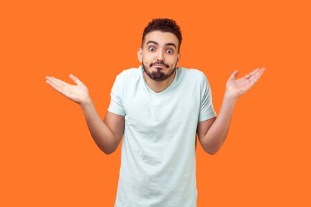 I don't know, who cares. Portrait of confused clueless brunette man with beard in white t-shirt shrugging shoulders, making no idea gesture, whatever. indoor studio shot isolated on orange background Stock fotó