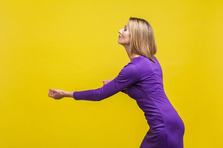 Side view portrait of assertive purposeful young businesswoman in elegant tight purple dress standing with raised fists, making effort to pull smth. indoor studio shot isolated on yellow background
