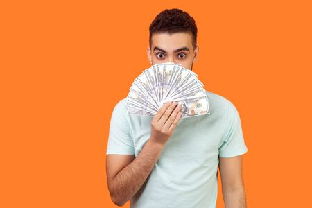 Portrait of positive young man in white t-shirt hiding half face with dollars, looking at camera with big amazed eyes, excited and surprised by lots of money. studio shot isolated on orange background