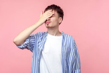 Facepalm. Portrait of distressed brown-haired man in casual striped shirt standing with hand on head, feeling regret and desperation, forgetful, bad memory. indoor studio shot, pink background Banque d'images