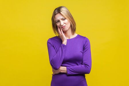 I'm bored! Portrait of indifferent thoughtful woman in elegant tight purple dress keeping hand on cheek and looking disinterested and dissatisfied. indoor studio shot isolated on yellow background