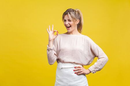 Portrait of satisfied beautiful young woman with blonde hair in casual beige blouse standing, looking at camera showing Ok sign gesture and winking, indoor studio shot isolated on yellow background Фото со стока