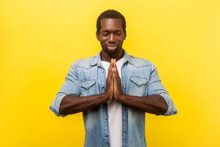 Harmony and relaxation. Portrait of peaceful young man in denim casual shirt holding arms in namaste, meditating with closed eyes and grateful calm expression. indoor studio shot isolated on yellow Stock Photo