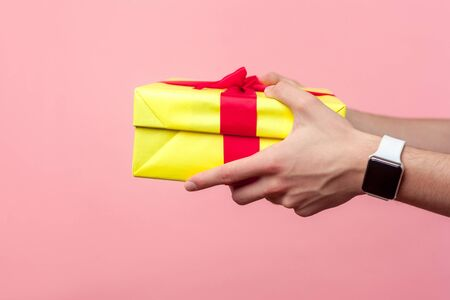Closeup of young male hands with wristwatches giving yellow gift box with red ribbon, sharing present on holiday, concept of charity and generosity. indoor studio shot isolated on pink background