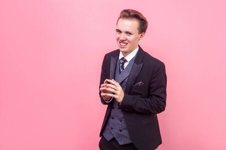 Portrait of devious sneaky sly businessman in suit and with stylish hairdo looking at camera with tricky cunning smile, thinking evil idea, meanness. indoor studio shot isolated on pink background Stock Photo