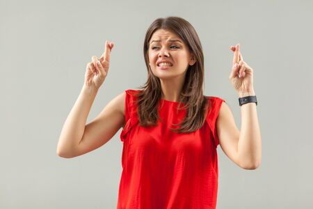 Hopeful and nervous. Portrait of worry brunette young woman in red shirt standing, clenching teeth, crossed fingers and hope to be winner . indoor, studio shot, isolated on gray background.
