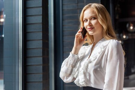 Portrait of smart devious businesswoman with long blond hair in stylish classic shirt talking on phone and smirking, looking aside with cunning expression, mulling over sly business plan, indoors