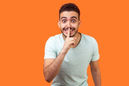 Please, keep silence! Portrait of positive brunette man with beard in casual white t-shirt standing asking to be quiet with finger on lips gesture. indoor studio shot isolated on orange background