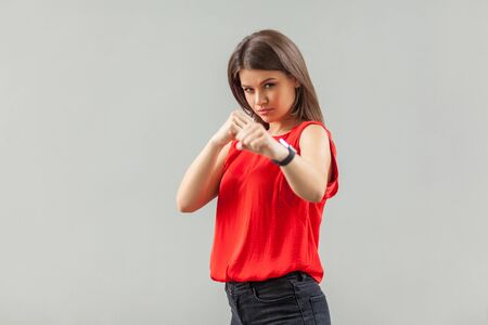 Portrait of serious beautiful brunette young woman in red shirt standing with boxing fists and looking at camera, ready to attack or defence. indoor, studio shot, isolated on gray background.