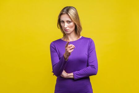 Bossy caution. Portrait of serious angry woman in tight purple dress pointing finger, showing warning gesture at camera, alarming to be careful. indoor studio shot isolated on yellow background Фото со стока