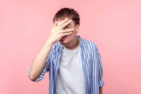 Portrait of shy curious brown-haired man with small beard and mustache in casual striped shirt looking through his fingers with wondered eyes, spying. indoor studio shot isolated on pink background