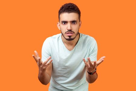 What do you want? Portrait of disgruntled annoyed brunette man with beard in casual white t-shirt standing with raised hands, mad indignant expression. indoor studio shot isolated on orange background