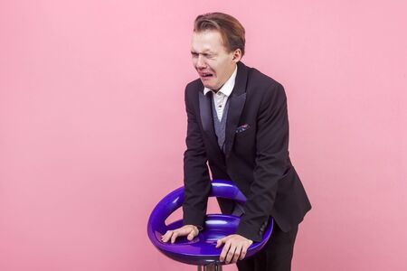 Portrait of dramatic desperate man in suit leaning on chair crying and screaming with grimace of pain and closed eyes, looking insulted deeply offended. indoor studio shot isolated on pink background