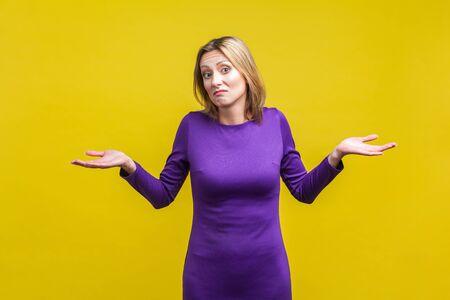 No lo sé, lo que sea. Retrato de mujer confusa incierta en vestido púrpura ajustado de pie con las manos levantadas, encogiéndose de hombros con desconcierto. Foto de estudio de interior aislado sobre fondo amarillo