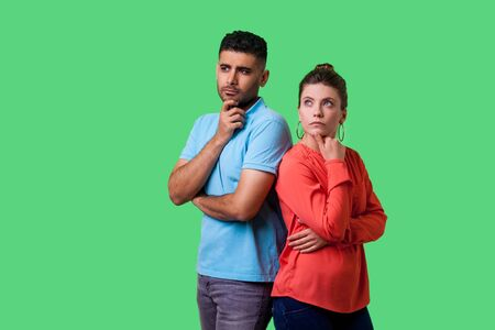 Think up plan! Portrait of smart attractive young couple in casual wear standing, holding their chins while thinking solution together, looking up. isolated on green background, indoor studio shot