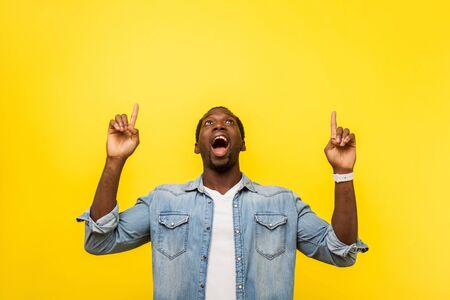 Wow, advertise there! Portrait of surprised happy man in denim shirt pointing up and looking above with amazed astonished expression, unbelievable news. studio shot isolated on yellow background