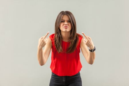Portrait of crazy angry brunette young woman in red shirt standing with middle finger sign and looking at camera with anger face. indoor, studio shot, isolated on gray background.