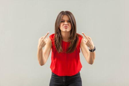 Retrato de mujer joven morena enojada loca en camisa roja de pie con signo de dedo medio y mirando a cámara con cara de ira. interior, tiro del estudio, aislado en fondo gris.