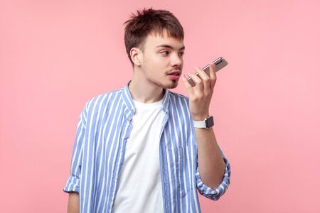 Voice application. Portrait of brown-haired man with small beard and mustache in casual striped shirt talking on phone, using digital vocal assistant for command recorder or calling. isolated on pink