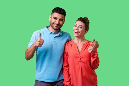 Portrait of positive attractive young couple in casual wear standing together, hugging as friends, showing thumbs up gesture and smiling at camera. isolated on green background, indoor studio shot