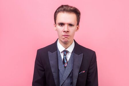 Portrait of upset stressed out businessman in tuxedo expressing disappointment or despair with pursed lips, is about to cry, hopeless sadness expression. indoor studio shot isolated on pink background Reklamní fotografie