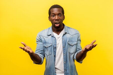 How could you. Portrait of unpleasantly surprised man in denim casual shirt standing with raised hands and amazed face asking whyd you do that, indignant annoyed expression. indoor studio shot Stock Photo