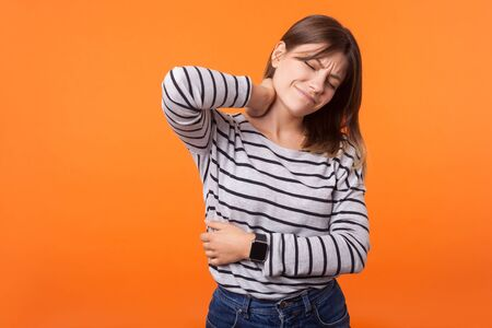 Portrait of tired sick woman with brown hair in long sleeve striped shirt standing with closed eyes, rubbing neck to relieve pain, muscle strain. indoor studio shot isolated on orange background Stock Photo