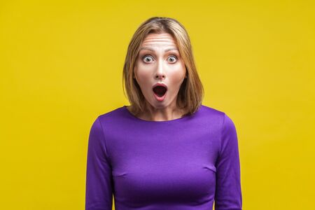 Wow, I can't believe this! Portrait of astonished woman with widely open mouth in amazement and big eyes looking at camera, stunned shocked face. indoor studio shot isolated on yellow background